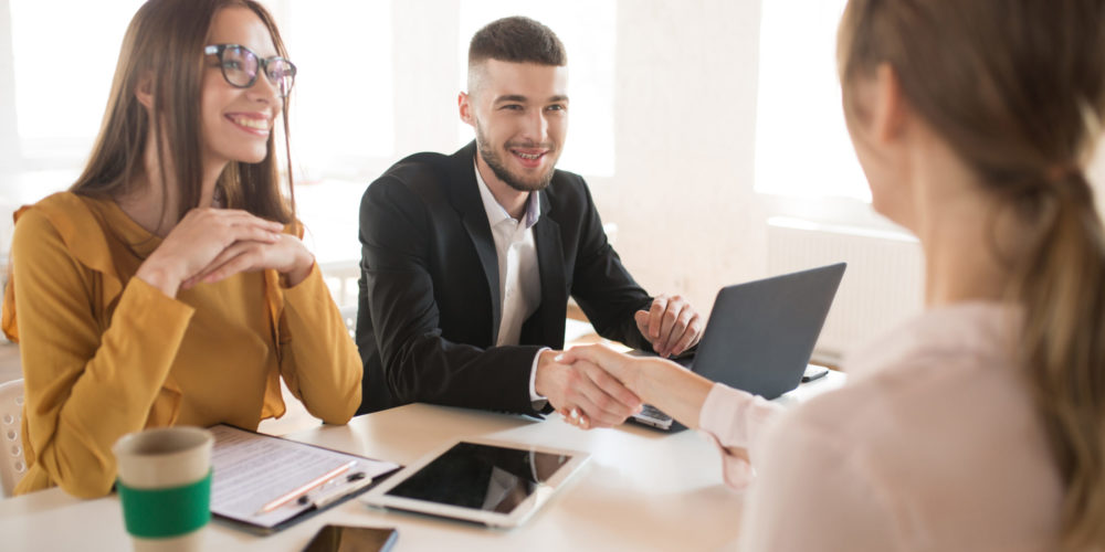Cheerful business man with laptop and business woman in eyeglasses happily talking with applicant about work. Young employers spending job interview in modern office